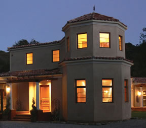 This is a photo of the Topanga Canyon Inn, a bed and breakfast in Topanga, California, built in the style of colonial Mexico with white stucco walls, arched openings, a red tile roof, paving and decorative tile work.